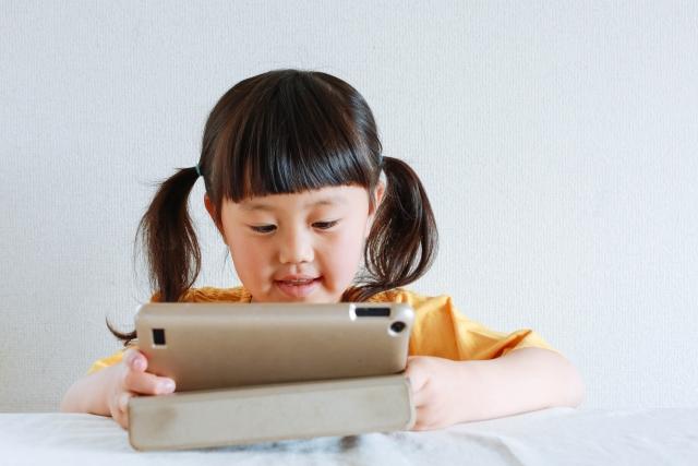 知育タブレットイメージ画像、タブレットで遊ぶ女の子